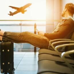 Mann am Flughafen blickt auf einen startenden Flieger